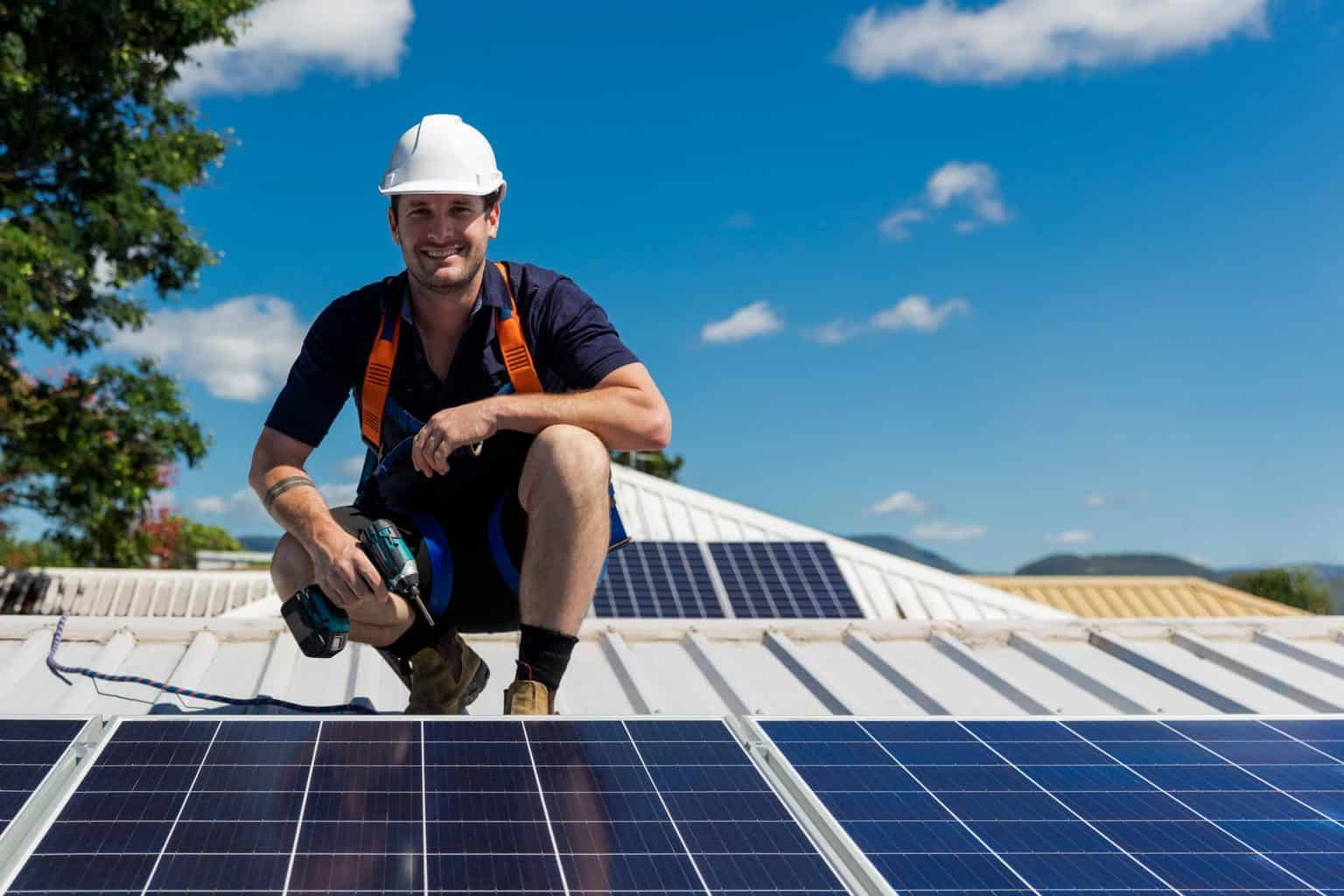 Man standing on roof next to solar panels